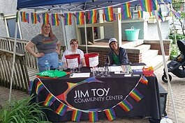Staff work a booth outside the Jim Toy Community Center's office.