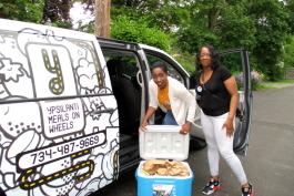 Staff drivers Ola Ibrahim and Traci Bibins load a van for YMOW's first Saturday delivery in 14 years.