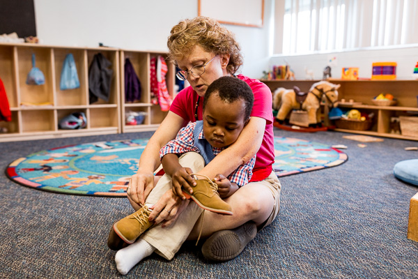 Michelle Smith helps put on a toddler's shoes