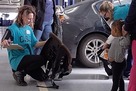 A safety technician inspects a child's car seat