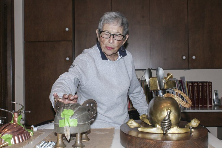 Rose Wunderbaum Traines works on metal sculptures on a counter in her kitchen.