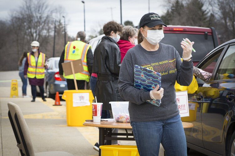 : Staff and volunteers work outside of the William and Janet Strickler Nonprofit Center to distribute food and emergency hygiene kits to those in need.