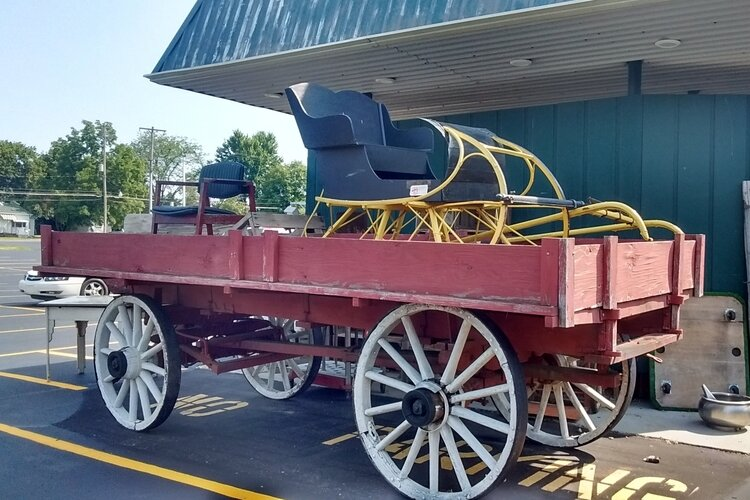 This freight wagon and sleigh are horse drawn vehicles from the late 19th century.  These and other large items are displayed outdoors in front of Antiques and Uniques.