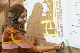 Art Reach intern Brianna Walter traces a banner for MAC TV Network on Tuesday, March 12, 2019.