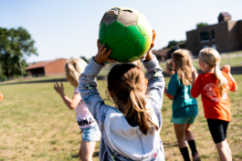 A girl gets ready to throw a soccer ball at PEAK after school program in Mt. Pleasant