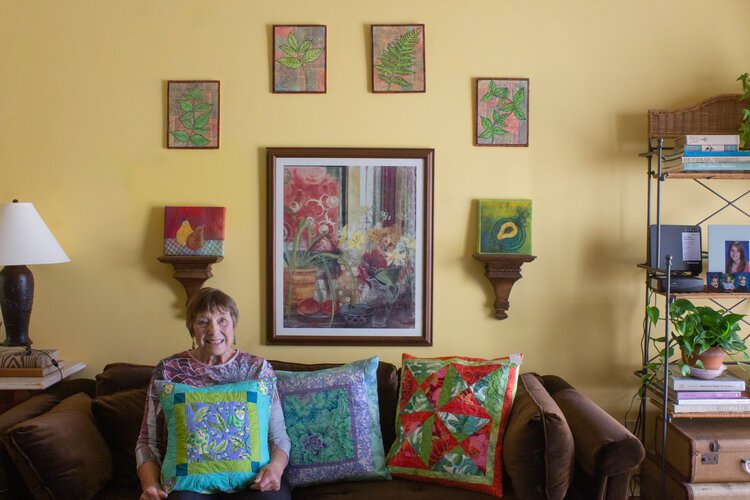"Virginia ""Ginny"" Crandall sits in her home, surrounded by pillows, wall hangings, and other fabric creations that she has made."