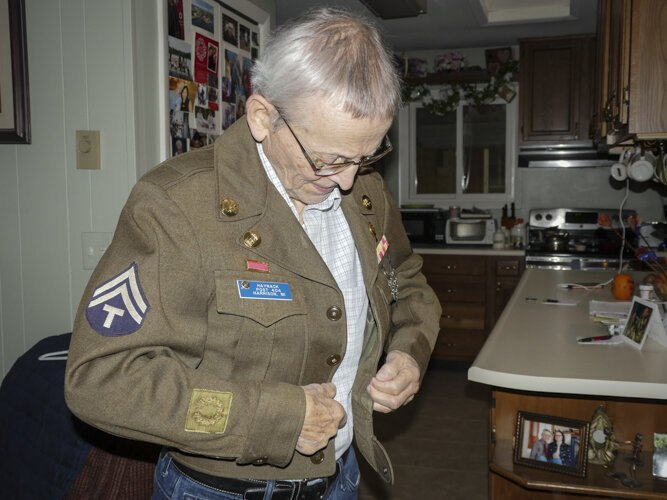 Ed Haynack buttons up his Army uniform from WWII.