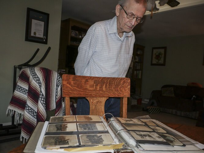 WWII veteran Ed Haynack, 91, looks at photos from his time in the Army.