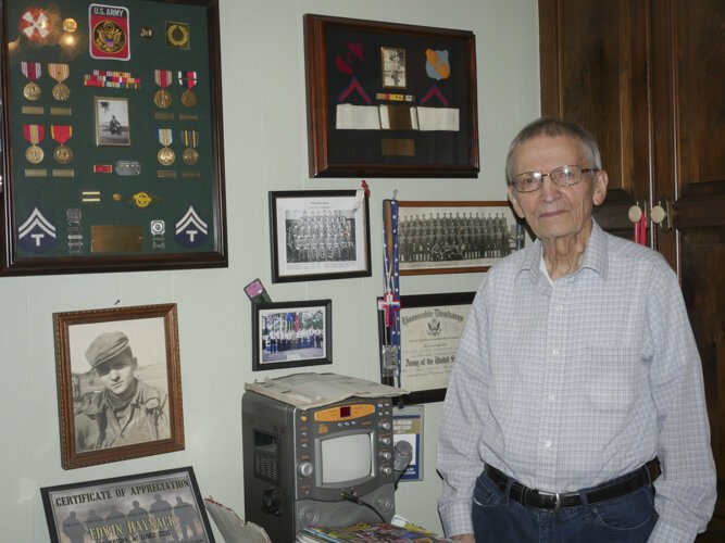WWII veteran Ed Haynack stands by his wall of memorabilia from his time in the Army.