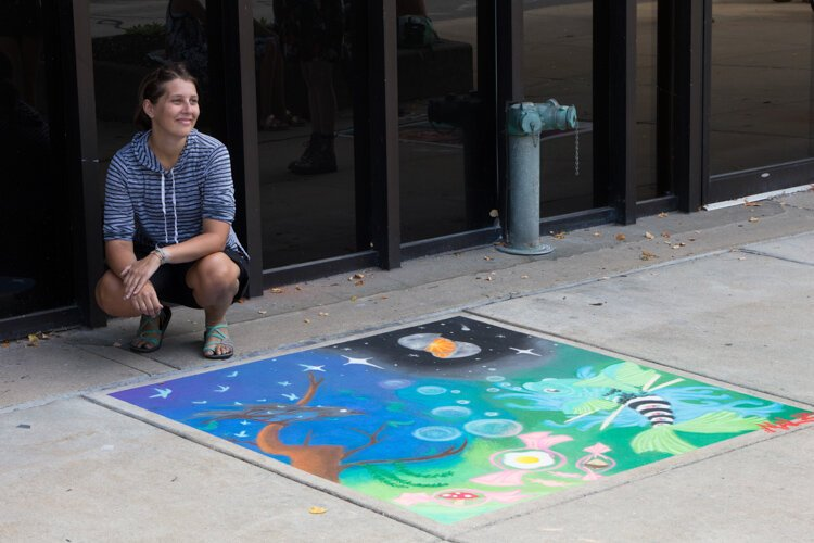 "First place Chalk the Walk winner Malia Reger poses with her artwork. ""I just kind of started drawing,"" she says. ""I did a sketch of it and I drew the fish first and then I just kind of kept with the surrealism and just kind of built it from there."""