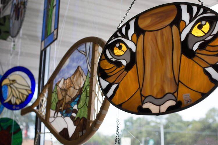 Stained glass art is displayed in the windows at Creatively! Glass & More.