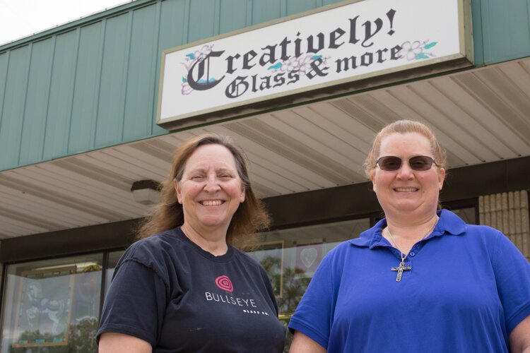 Owner Jean Holland (right) and her employee Sharon Holzhausen pose for a photo outside Creatively! Glass & More.