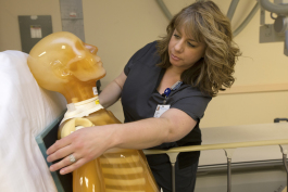 Mid Michigan College Radiology student Julie Corcoran adjusts an x-ray detector behind their anthropomorphic full body phantom the class uses.