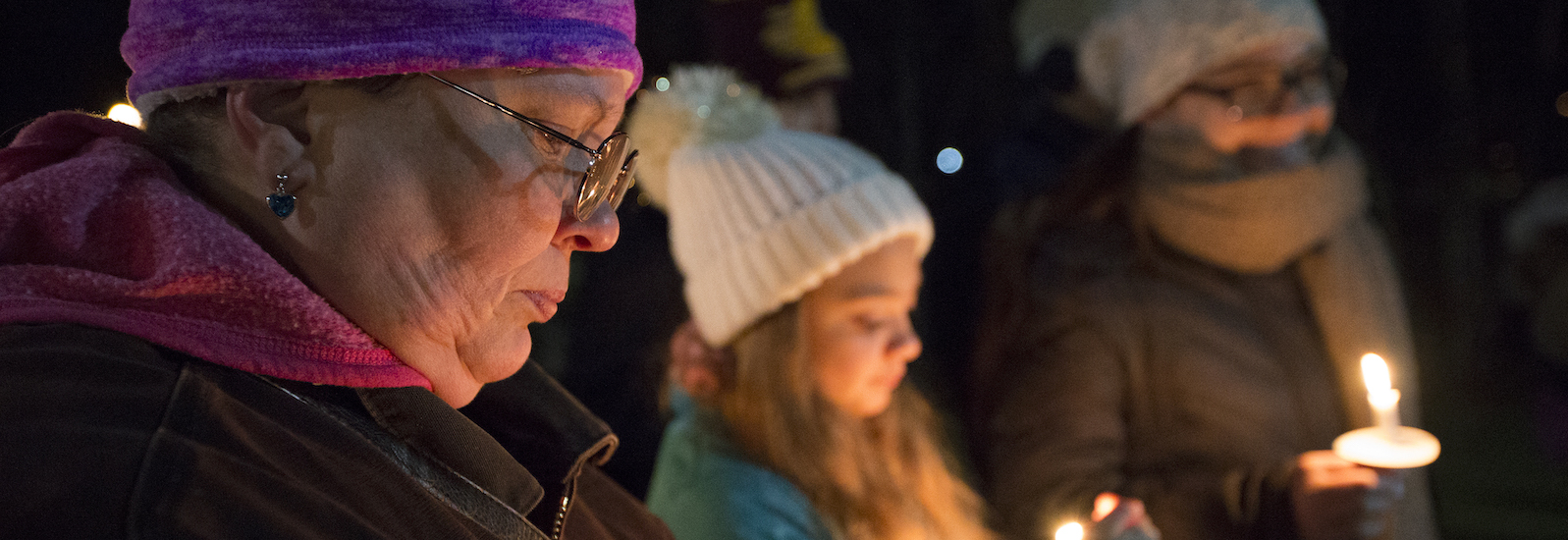 Renee Benner protects her candle from the wind at a homeless awareness event at Central Michigan University on Wednesday, Nov. 15, 2017.