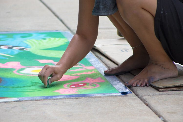 Chalk the Walk artist Malia Reger touches up her artwork before it is judged.