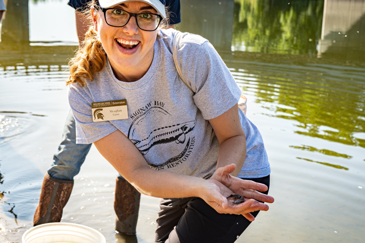 Meaghan Gass, Michigan Sea Grant Extension Educator with MSU Extension with a sturgeon for release.