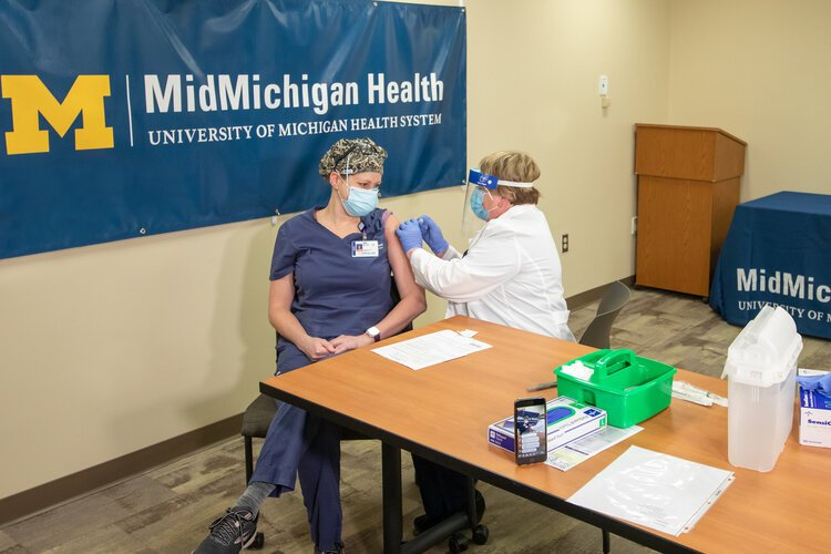 This week, the COVID-19 vaccine was delivered to MidMichigan Medical Center – Midland. Shortly after the vaccine was delivered Wednesday morning, the first dose was given to AJ Schafer, R.N., a medical ICU nurse, of Weidman, Michigan.