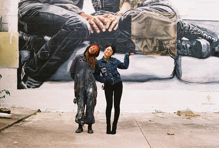 "Bakpak Durden and Cyrah Dardas stand in front Durden's mural titled ""a constellation in winter"" located at the LGBT Center in Detroit."