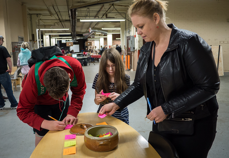 "Alisha Sidebottom of Fenton (right) as well as Gabriel Wright, 14, and her sister Aurora Wright, 11, both of Flint, vote for their favorite presenter at Flint SOUP during the October event at Factory Two in Flint. All votes were collected in the ""tac"