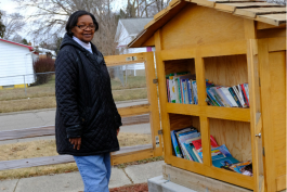 Jeanette Edwards, founder and president of the Brownell-Holmes Neighborhood Association, stands near the little library the block club built two years ago.