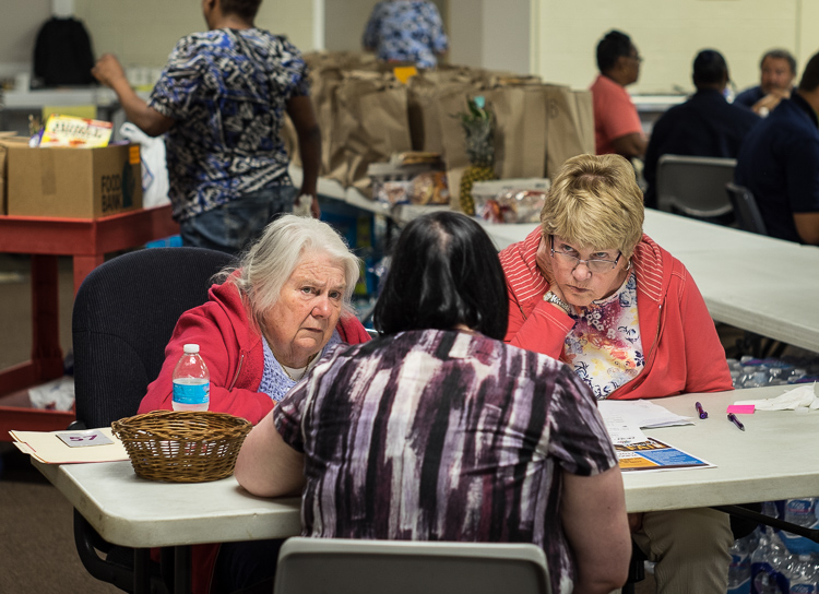 Volunteers Gaytra Molinari of Millington (left) and Elizabeth Alunno of Flushing Township (right) talk with program manager Julie Chuchvara at St. Luke's intake screening station. Here, patrons are approved to receive food.