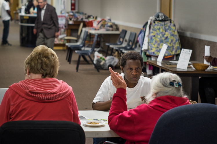 Marie Humphrey of Flint answers questions at an intake screening before receiving a food packet at St. Luke's.