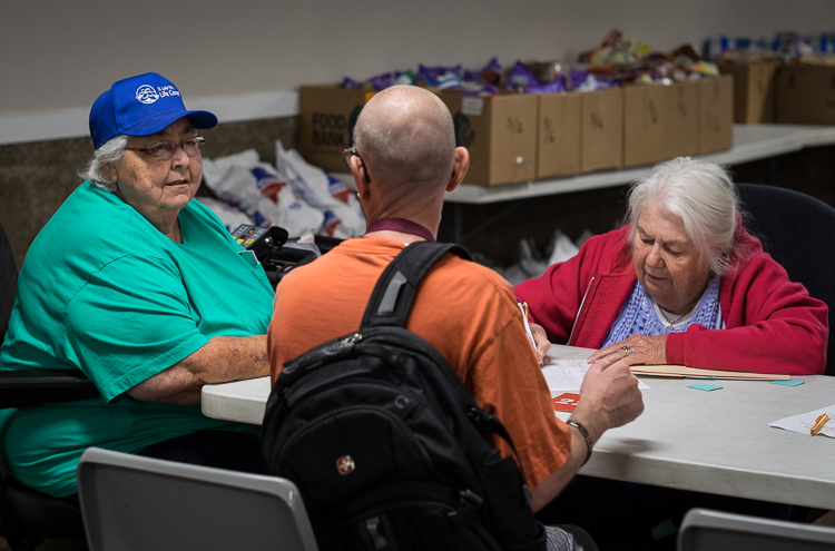 Co-founder Sister Judy Blake (left) speaks with a patron at the intake screening station at St. Luke's on Tuesday. At right is volunteer Gaytra Molinari of Millington.