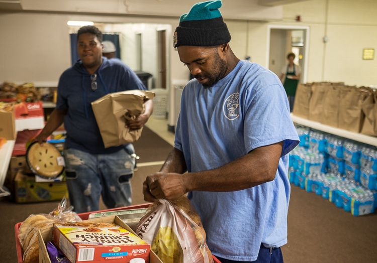 Antonio McNeal, food pantry supervisor at St. Luke N.E.W. Life Center assembles a food box that will be given to a family.
