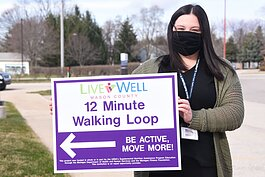 Erin Barrett holds a walking trail sign in Ludington.