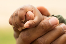 Parent holding infant's hand