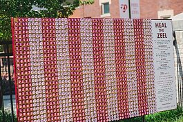 The interactive exhibit, located on the corner of Main Avenue and Elm Street, takes the shape of a wall made up of red and white campaign-style buttons.