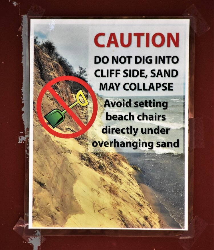 Warning signs alert visitors to dangers of beach erosion at Ottawa County lakeshore parks.