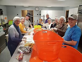 Kids Food Basket volunteers pack meals at Peace Lutheran Church in Holland.