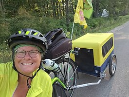 Avid cyclist Betsy Cech on her recumbent triker with her dog, Clara, in tow.
