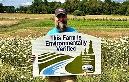 Greg Dunn's Blackbird Farm in Coopersville received MAEAP verification in 2020. Dunn shows off his new sign in one of their produce fields.