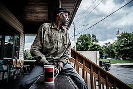 A stand member looks out across the neighborhood from the Porch of The Lemonade Stand of Muskegon.