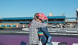 Jon Ornée hugs his dad after setting a new world record for a 100-mile bike ride while drafting.