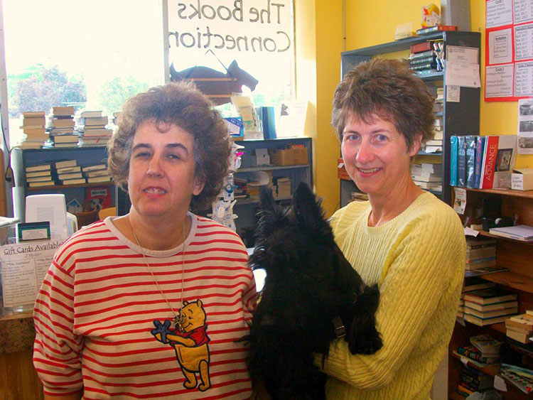 The Books Connection manager Charlotte Grombelski and owner Kathleen Mahinske pose with Darby.