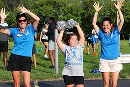 Friendship Cheer Program instructors Kathy Smith and Maria Streberger cheering with Gracie Trocino.