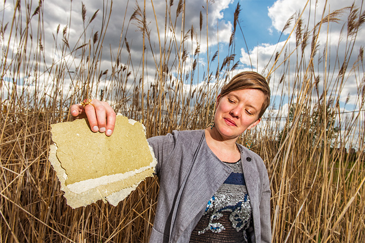 Meg Heeres models phragmites paper near a stand of the invasive plant near Canfield and Grand River.