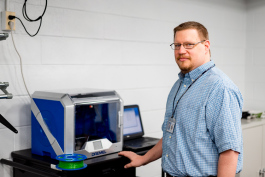 Mark Hancock next to the library's 3D printer