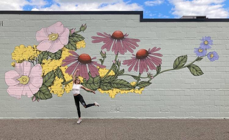 The new mural on The Vines Flower and Garden Shop with artist Mackenzie Harthun
