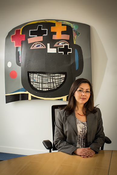 Leila Matta, Art Programs Manager, sits in an executive conference room at the Mercedes-Benz Financial Services headquarters. In the background is a painting from Tyree Guyton's Heidelberg Project which is part of the company's permanent art collecti