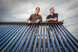 L to R Jacob Corvidae and Conan Smith with a solar water heater on the roof of the Washtenaw County Administration Building