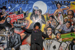 Marsha Battle Philpot pointing out her father's record store and her father in Curtis Lewis' mural at Bert's Warehouse Theatre
