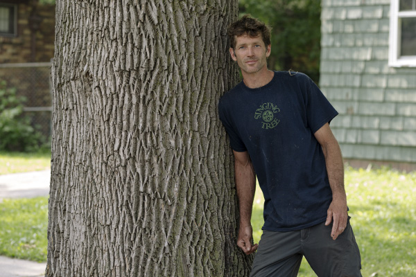 Kevin Bingham stands next to a healthy ash tree in front of his home