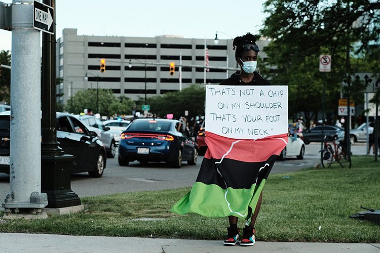 A protester holds up a sign Friday in Detroit.