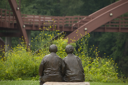 A sculpture  looks toward the Tridge in Midland, MI