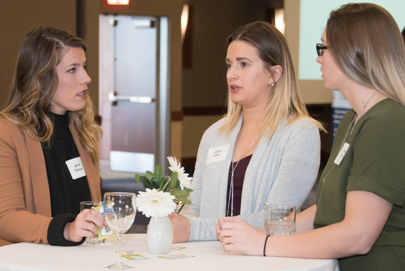 Casual conversations keep the Coming Home event from feeling like a traditional job fair. During the 2018 event, participants gathered at high-top tables.