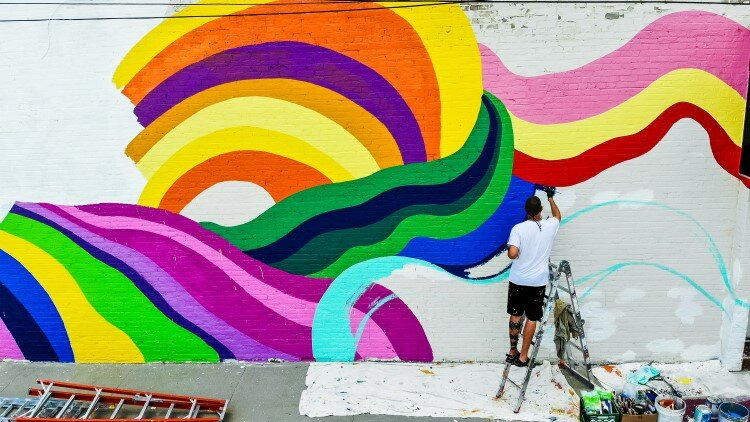 A new mural being painted on the exterior of Live Oak Coffeehouse is one of the many artistic additions.